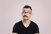 Young male with glasses and mustache, grey background, studio shot, raised eyebrow