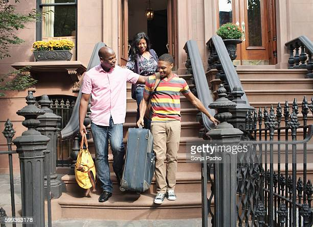 Young man with parents leaving for college on front stoops