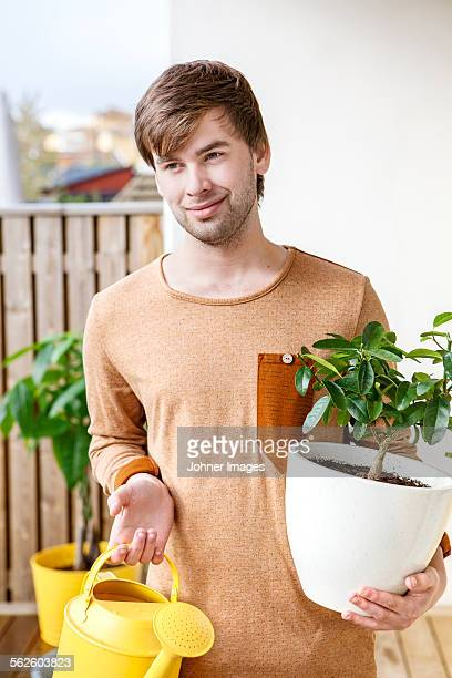 Young man with plant in pot