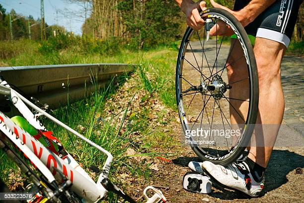 young man with racing bike repairing flat tire at roadside