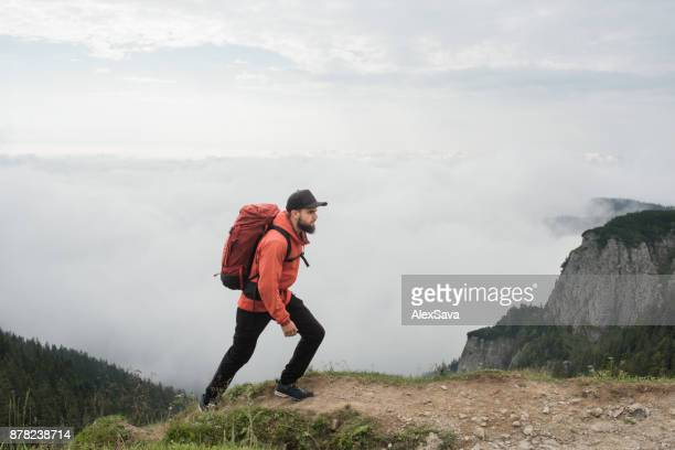 Young man with red backpack trekking in mountains