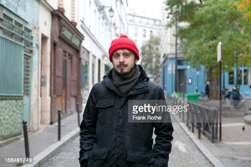 young man with red cap stands at street : Stock Photo