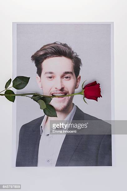 Young man with rose in his teeth