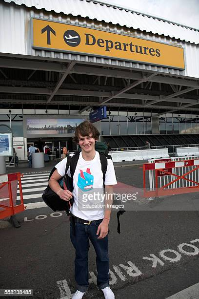 Young man with rucksack outside Departures Heathrow airport London
