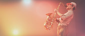 Young man play saxophone on the stage in the colorful highlights. This is a 3d render illustration