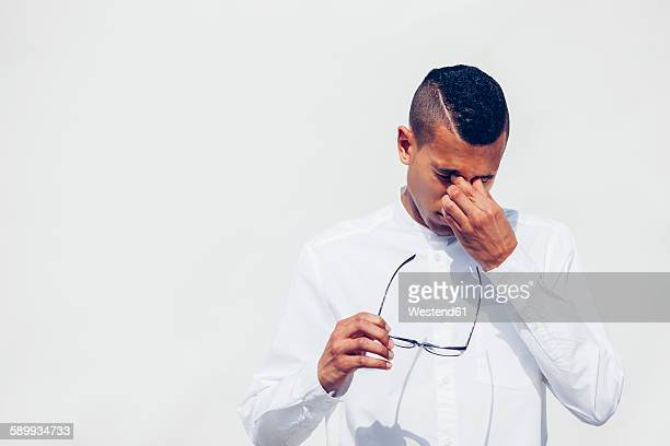 Young man with shaved hair holding glasses in his hand while rubbing eyes in front of white background