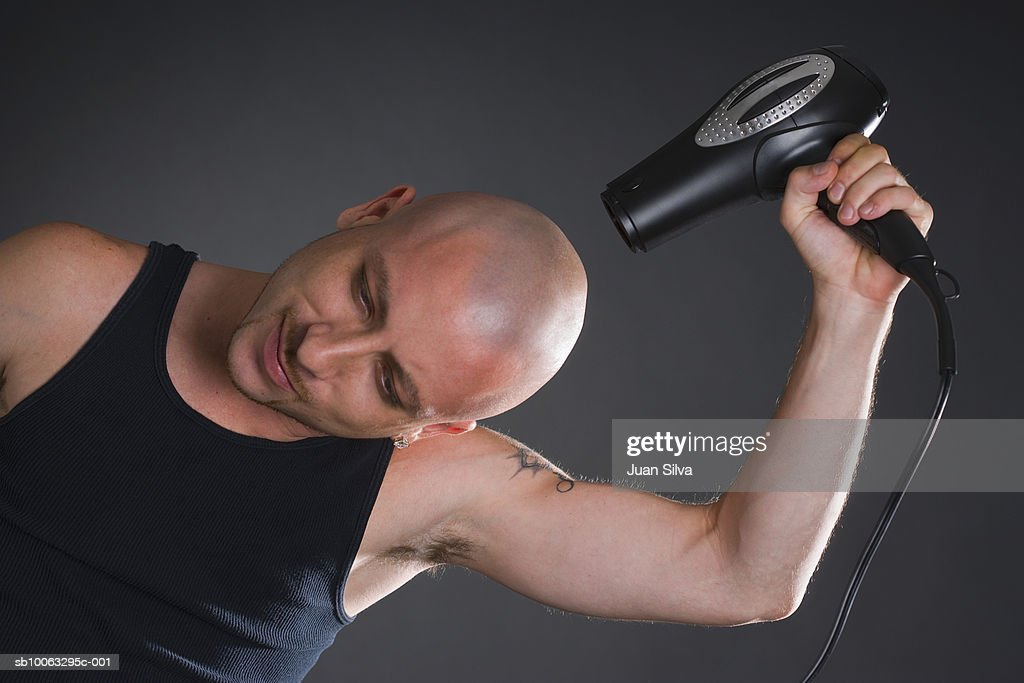 Young man with shaved head posing with hair dryer, studio shot : Stock Photo