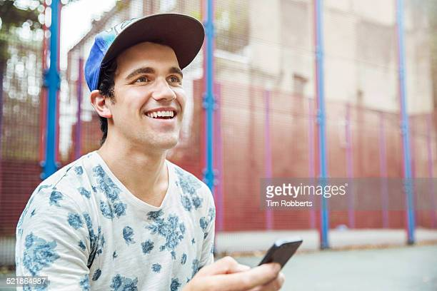 Young man with smart phone at basket ball court.