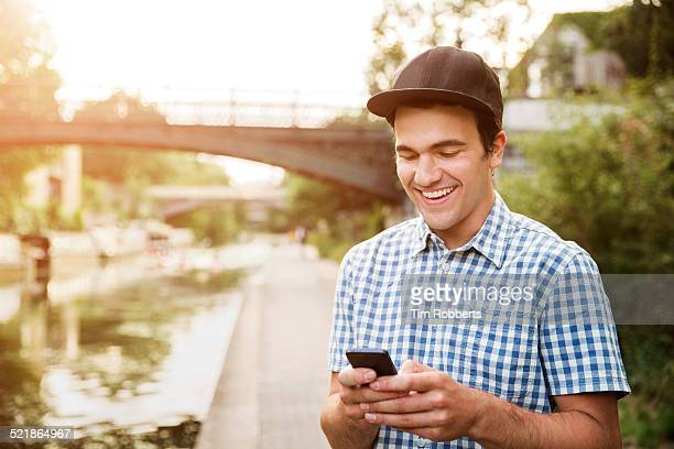 Young man with smart phone on canal.