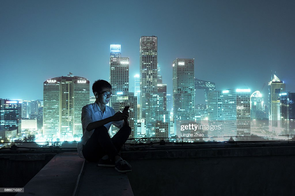 Young man with smartphone sitting on roof : Stock Photo