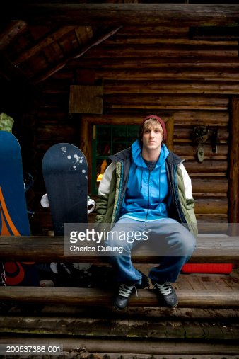 Young man with snowboards sitting on railing outside log cabin : Foto de stock