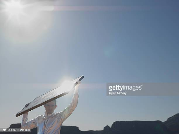 Young man with solar panel, portrait