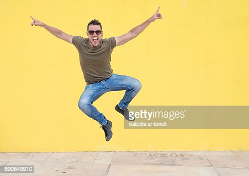Young man with sunglasses jumping in front of a yellow wall. : Stock Photo
