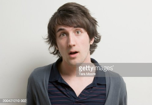 Young man with surprised expression on face, portrait, close-up : Stock Photo