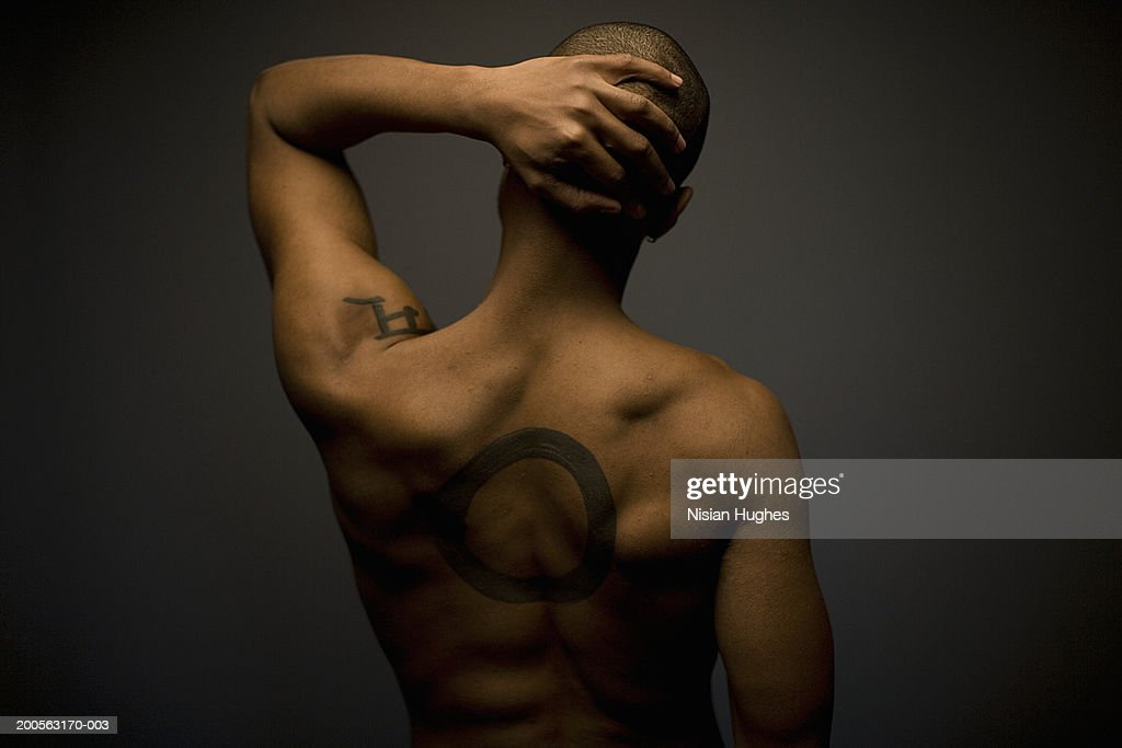 Young man with tattoo on back, rear view : Stock Photo