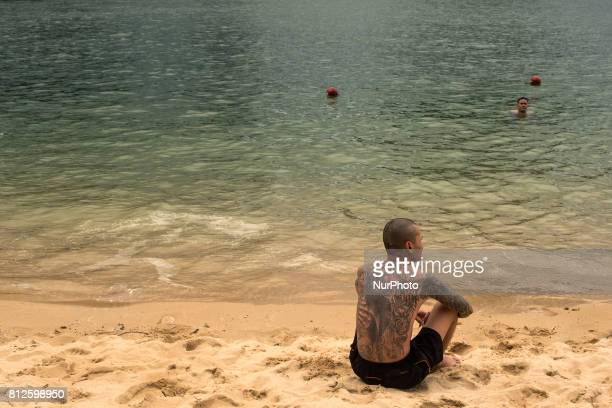 A young man with tattoos enjoys one of the many beaches in Halong Bay The bay of Ha Long is an extension of water of approximately 1500 km ² Located...