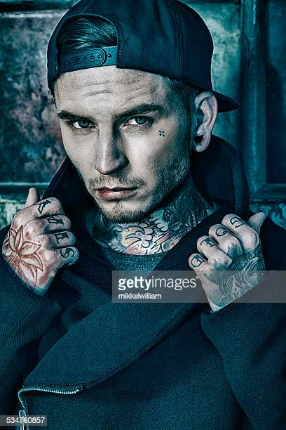 Young man with tattoos on neck and hands
