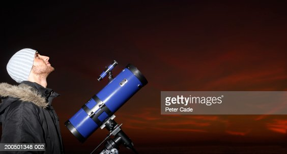 Young man with telescope looking at sky, dusk, side view : Stock Photo