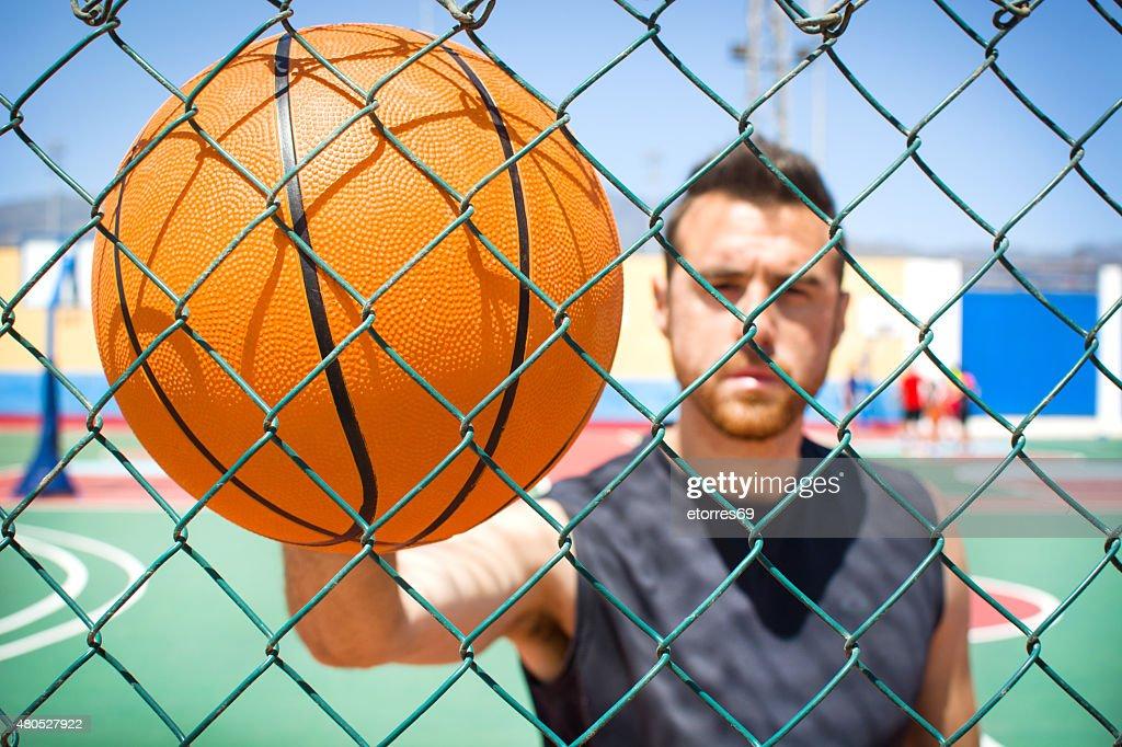 Junger Mann mit der basketball hinter einem Zaun : Stock-Foto