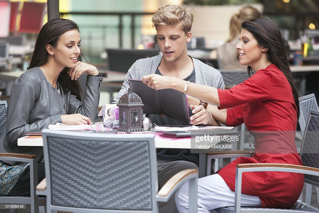 Young man with two young women looking at menu in a restaurant : Stock Photo