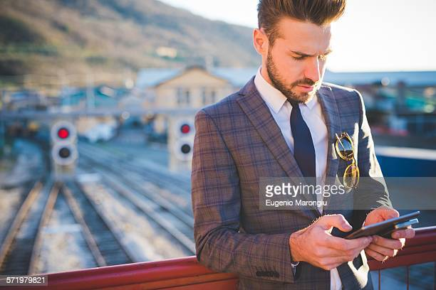 Young man with using digital tablet on railway footbridge