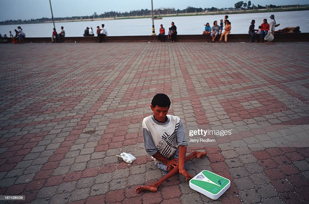 A young man, with what is probably polio, makes money charging people to use his scale in the evenings along the riverfront in Phnom Penh..
