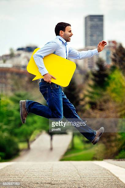 Young man with yellow speech bubble jumping outdoors