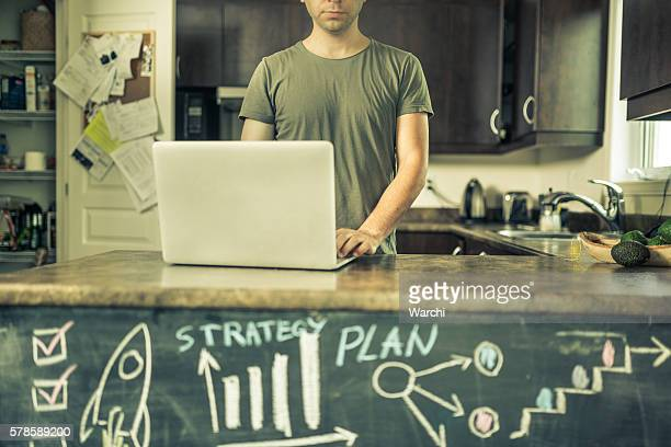 Young man working at home in the kitchen