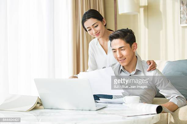 Young man working at home while his wife looking at him