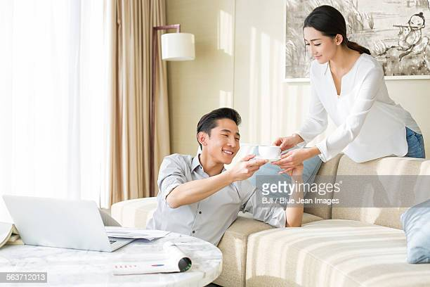 Young man working at home with his wife serving coffee