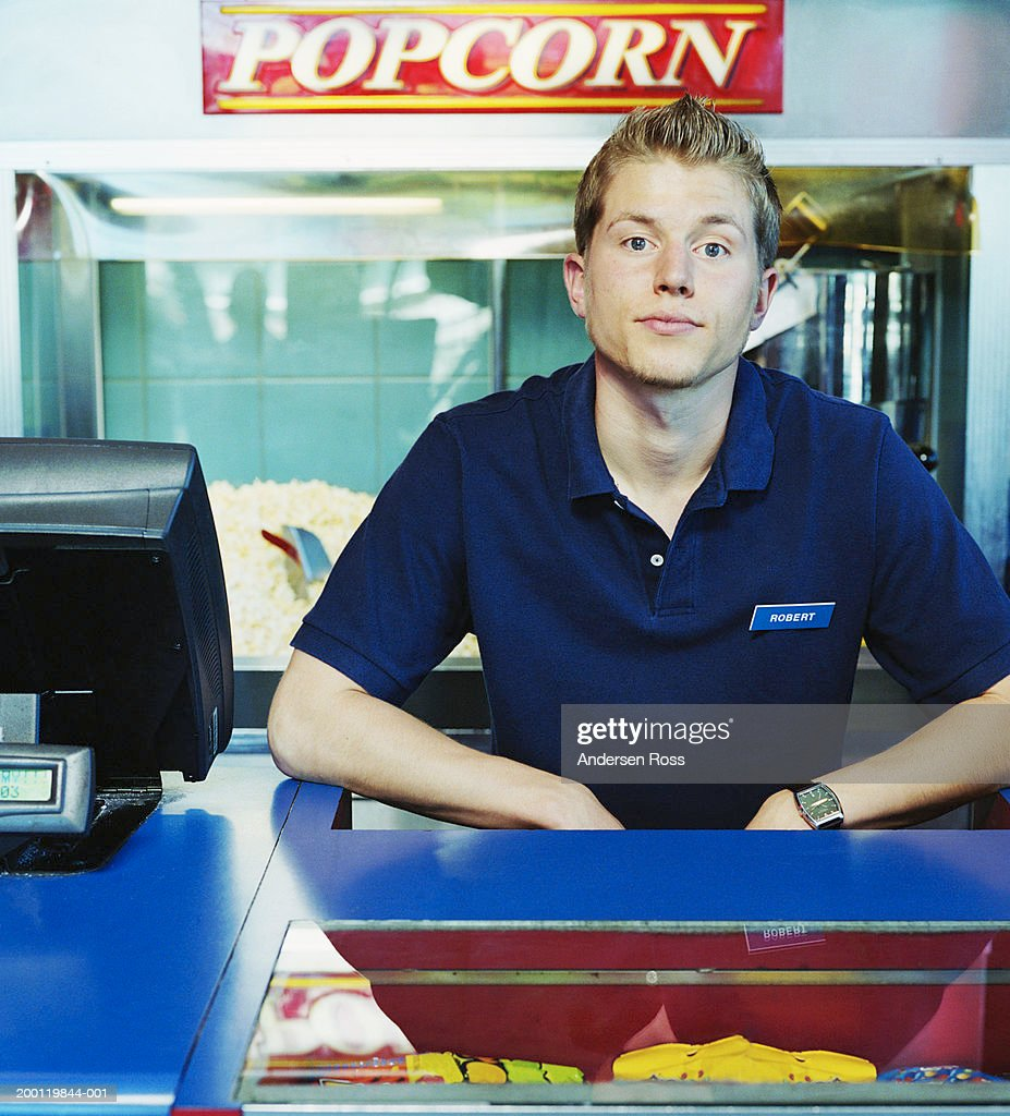 Young man working at movie theater concession stand, portrait : Stock Photo