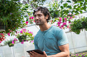 A young man working in a plant nursery,surrounded by flowering plants.