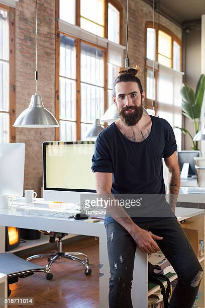 Young man working in a start up office smiling portrait