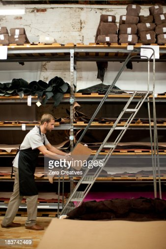 Young man working in leather stockroom
