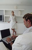 Young man working on a laptop with a young woman standing in front of him