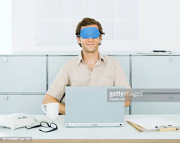 Young man working on laptop in office wearing eye mask