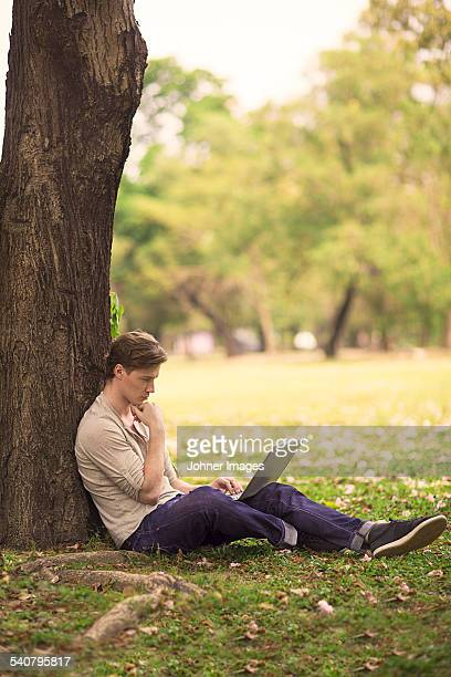 Young man working on laptop outdoor