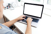Image of a young man at computer desk, working on laptop