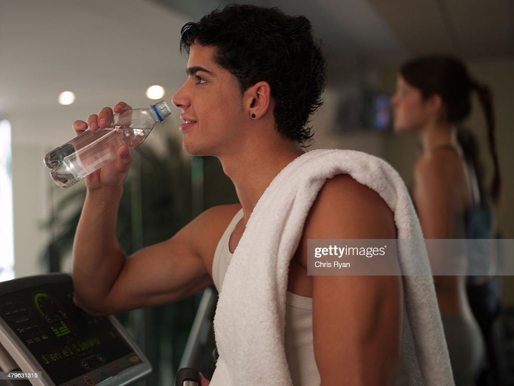 Young man working out on step machines at a health club : Stock Photo