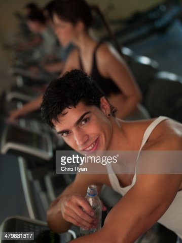 Young man working out on step machines at a health club