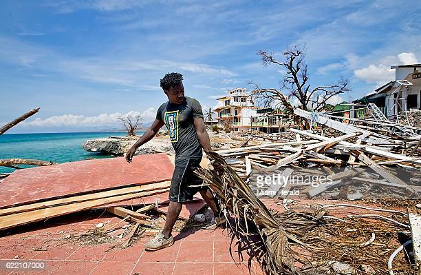 A young man works to remove debris from the damaged beachfront Dan's Creek hotel in Port Salut Haiti on October 11 2016