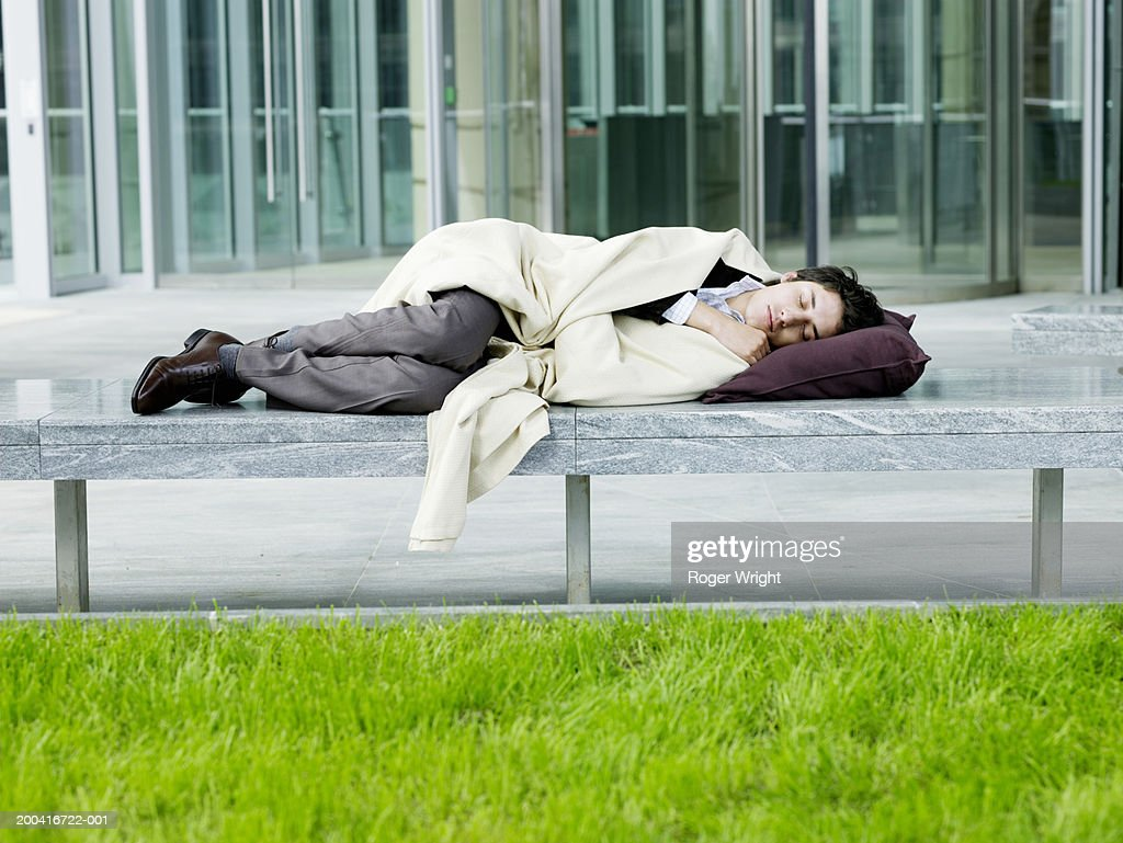 Young man wrapped in blanket asleep on bench, head resting on cushion : Stock Photo
