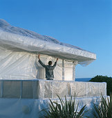 Young man wrapping house in bubble wrap