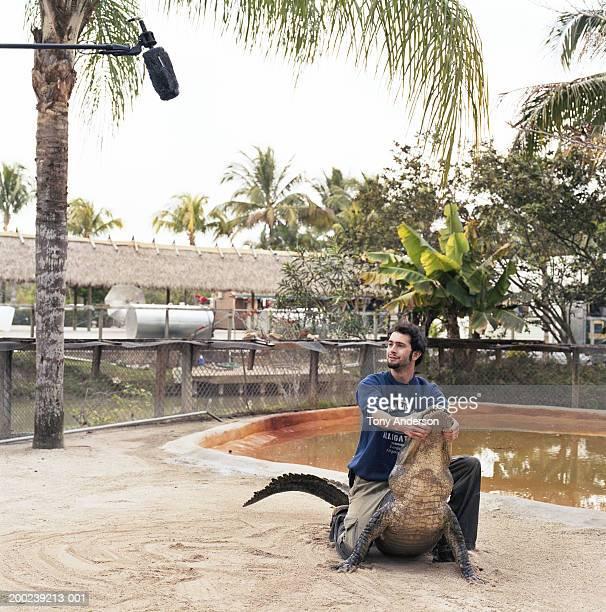 Young man wrestling alligator under microphone at alligator farm,