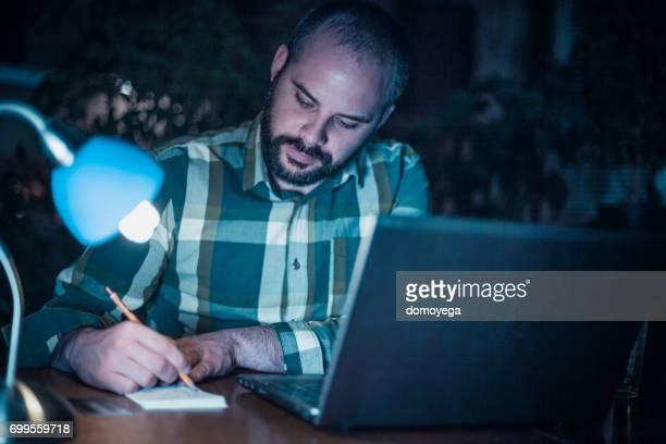 Jonge man schrijven en met behulp van laptop bij nacht