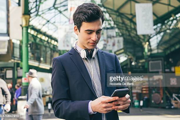 Junger Mann Schreiben auf dem Smartphone