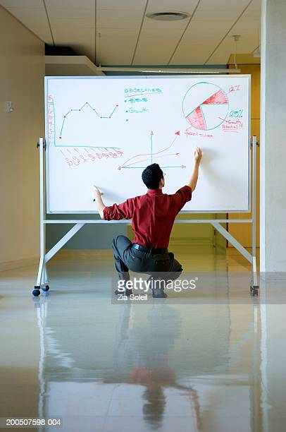 Young man writing on white board, rear view