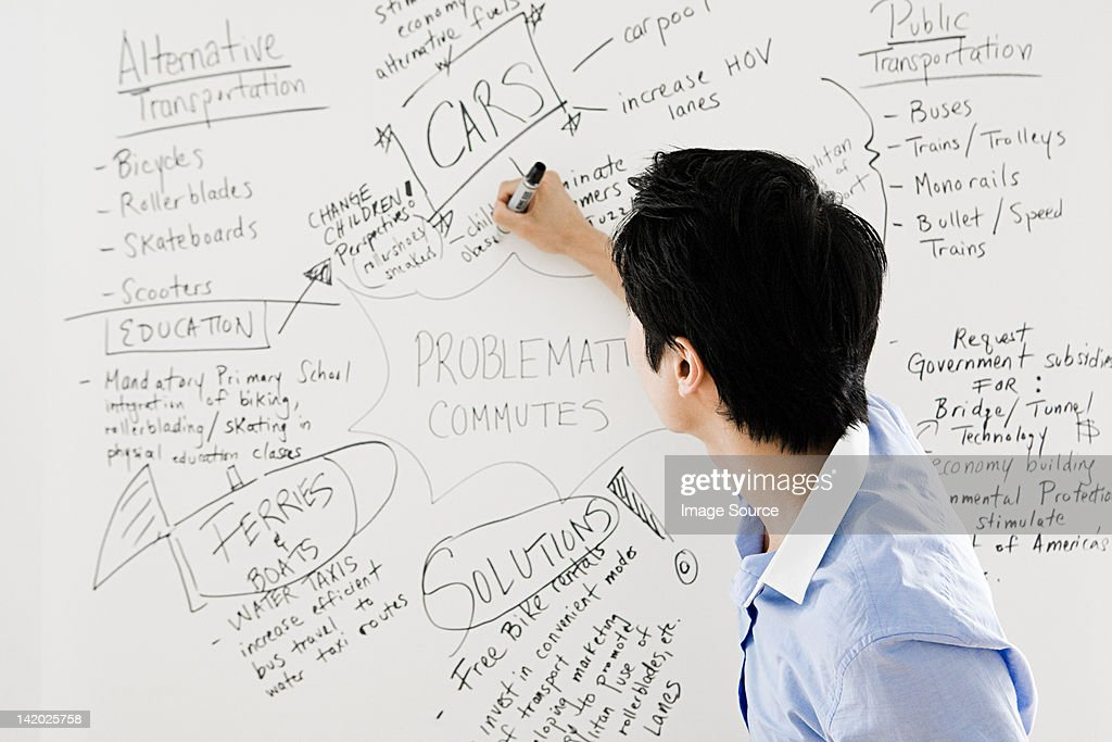 Young man writing on whiteboard : Stock Photo