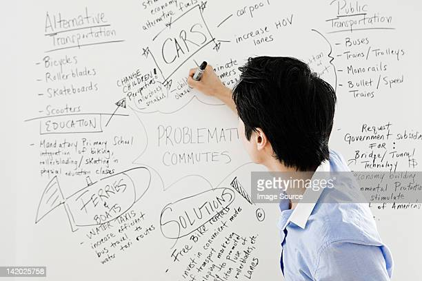 Young man writing on whiteboard
