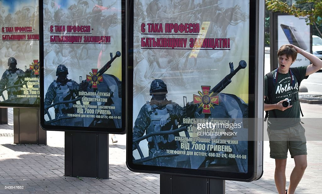 A young man yawns as he passes by advertising placards of Ukrainian Military Forces reading 'There is such a profession to defend the homeland', set in the centre of Kiev calling to serve in the army, on June 29, 2016. A Ukrainian opera singer who performed for two decades in France before joining Kiev's volunteer forces fighting pro-Russian insurgents has been killed in the separatist east, officials said on June 29. / AFP / Sergei SUPINSKY